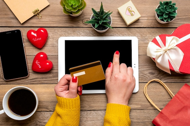 Girl holds tablet, debit card, chooses gifts, makes purchase, coffee cup, two hearts, bag on wooden table