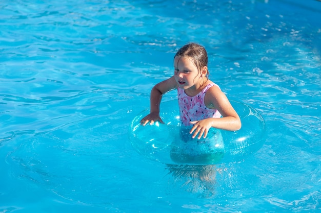 The girl holds on to a transparent blue inflatable circle with her hands and has a good time on vaca...