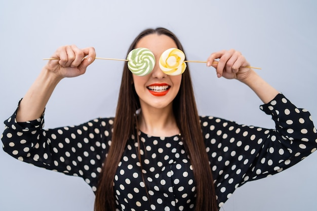 Girl holds two lollipops near eyes. cheerful lady in dotted shirt over white background.