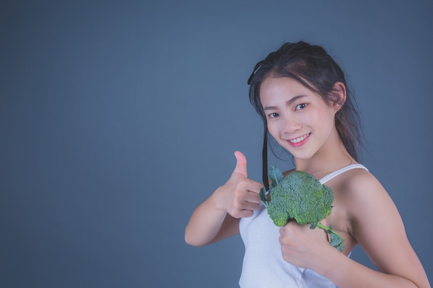 Girl holds the vegetables on a gray background.