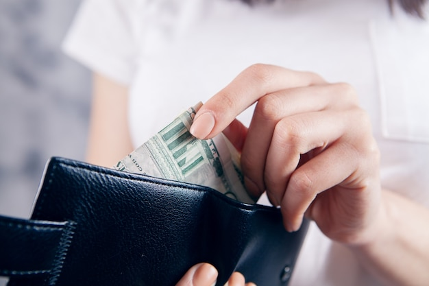 Girl holds wallet in her hands and takes money