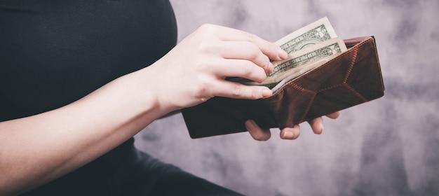 女の子は彼女の手に財布を持ってお金を取る