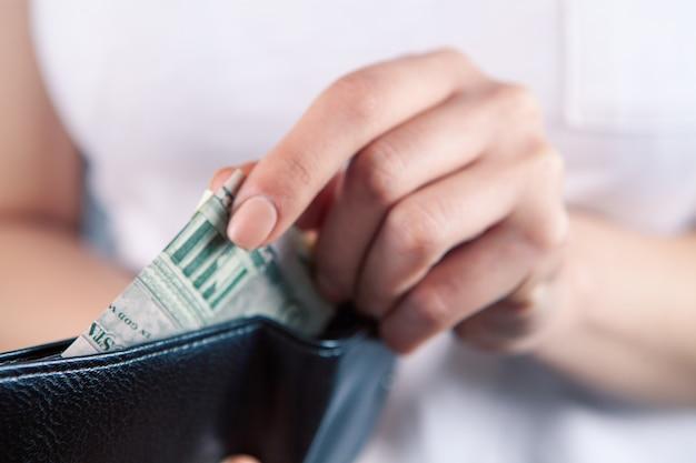 소녀는 그녀의 손에 지갑을 보유하고 돈을 걸립니다