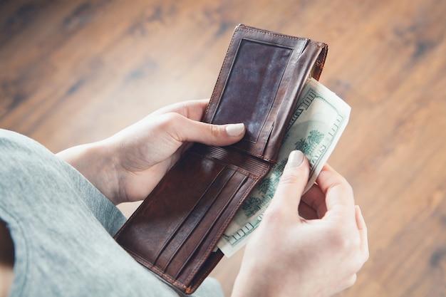 Девушка держит в руках кошелек и берет деньги