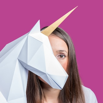 The girl holds a white 3d papercraft model of unicorn minimal art concept