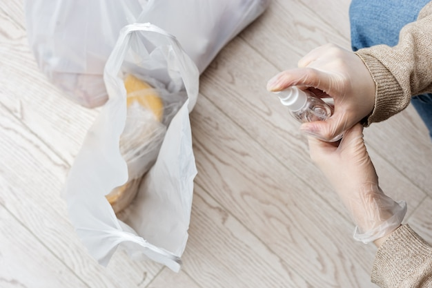 Girl in home clothes and rubber gloves on her hands disinfects surface of plastic bags with products from store.