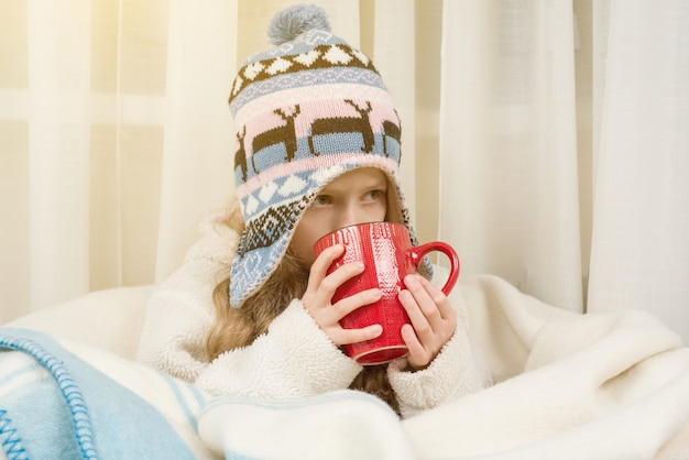 Girl at home in knitted hat wrapped in rug, drinking hot tea