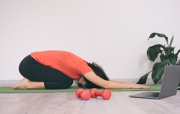 Girl at home on a sports mat doing a workout