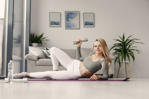 Girl at home. woman make yoga. lady with dumbbells and water.