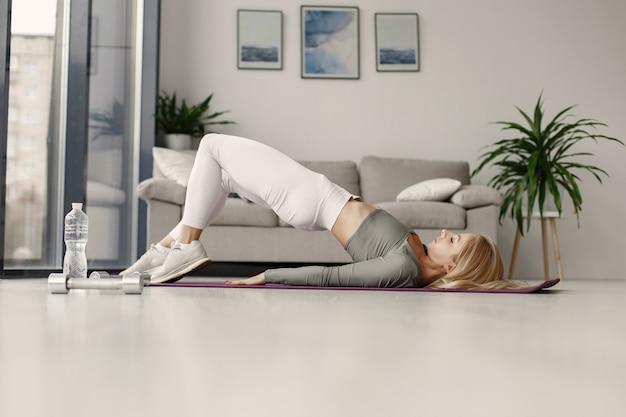Ragazza a casa. la donna fa yoga. signora con manubri e acqua.