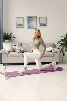 Ragazza a casa. la donna fa yoga. signora con manubri.