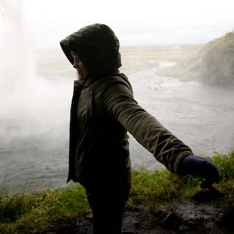 Girl in hooded coat standing in profile with arms spread before steamy body of water