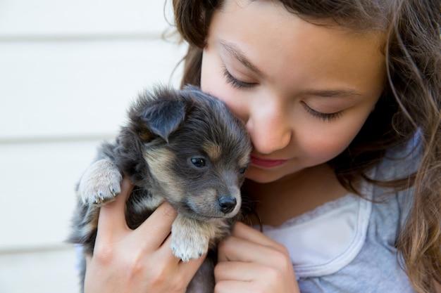 Девочка обнимает маленького щенка седого волосатого чихуахуа