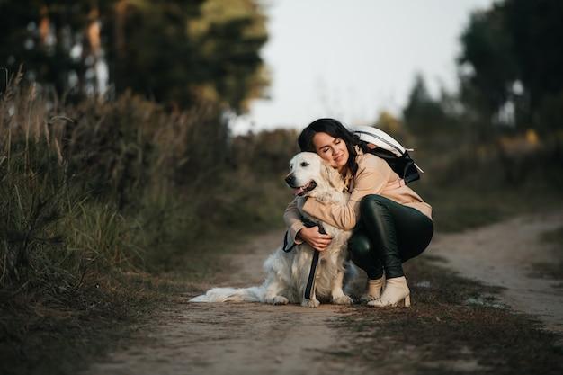 森の中でゴールデンレトリバー犬を抱き締める少女
