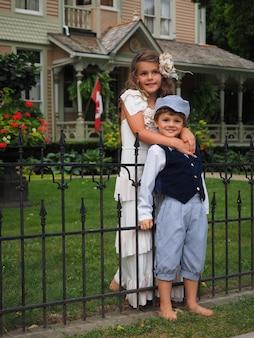小さな男の子を肩から抱きしめる女の子