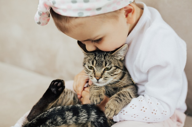 Девушка обнимает и целует полосатую кошку