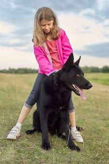 大きな黒い犬の羊飼い、子供、ペットを自然の中を歩くハグの女の子