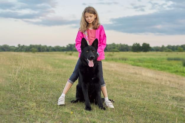 大きな黒い犬の羊飼い、子供とペットが自然の中を歩いて抱き締める女の子