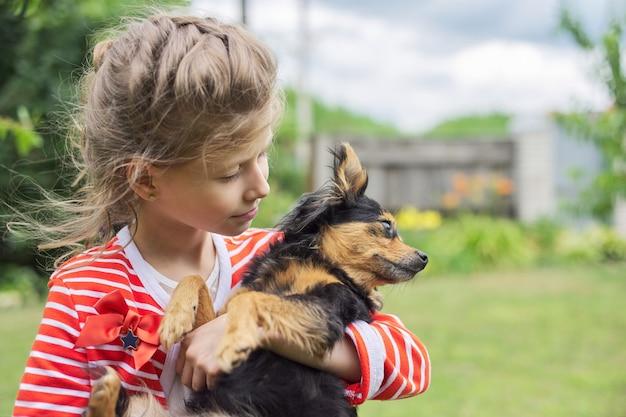 屋外で犬を抱き締める女の子