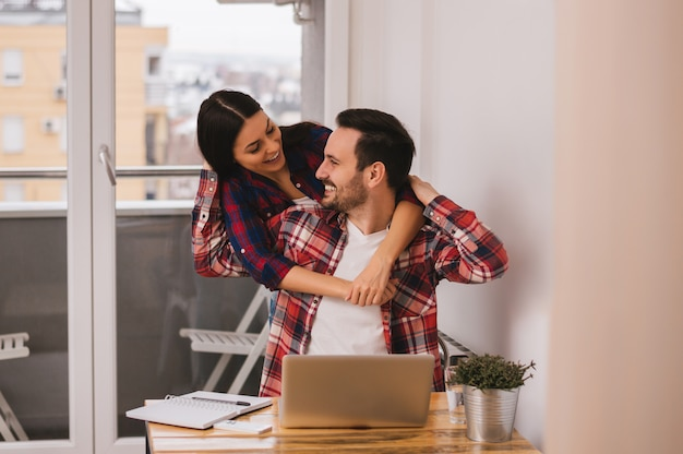 Girl hugging her boyfriend while he working at home office