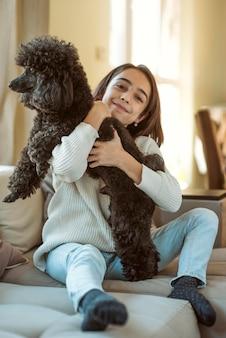 Девушка обнимает собаку во время карантина