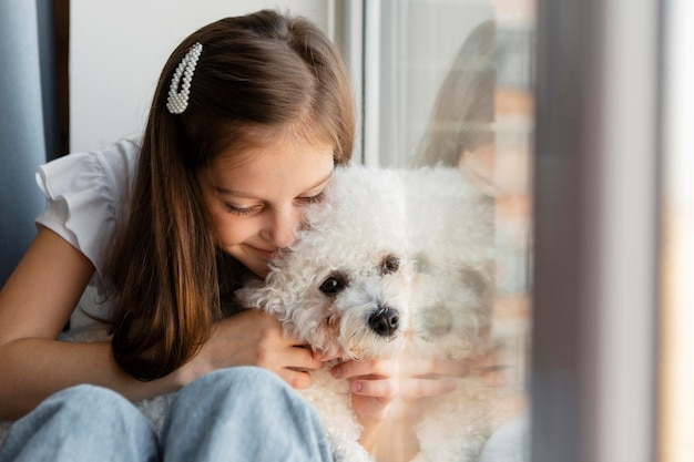 Girl hugging her dog next to a window