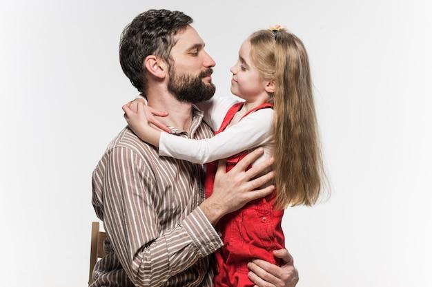 白い壁に彼女の父親を抱き締める女の子