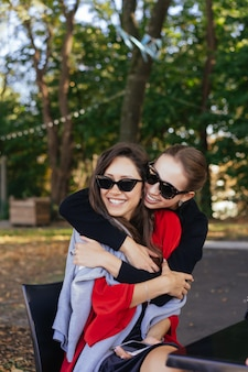 Girl hugging her friend. portrait two girlfriends in the park.