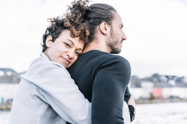 Girl hugging her partner  back with the  sea out of focus