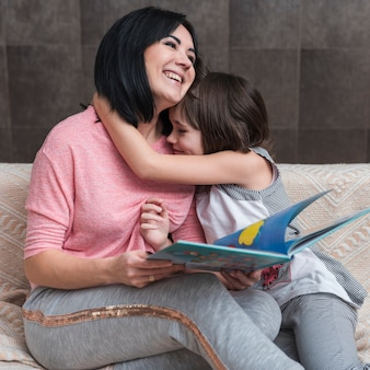 Girl hugging mother with book on couch