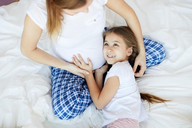 妊娠中のママを抱き締める女の子