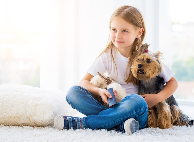 Девушка обнимает собаку терьера и игрушку в помещении