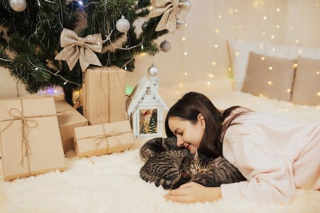 3匹の眠っている縞模様の子猫を抱き締める少女