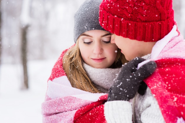 Girl in hugs of her boyfriend in winter forest