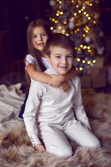 Девушка обнимает своего брата, сидящего на кровати в студии на рождество