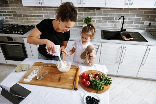 女の子はぬいぐるみを抱きしめ、母親がボウルに注ぐ小麦粉を混ぜます。一緒に料理をする母と娘 Premium写真