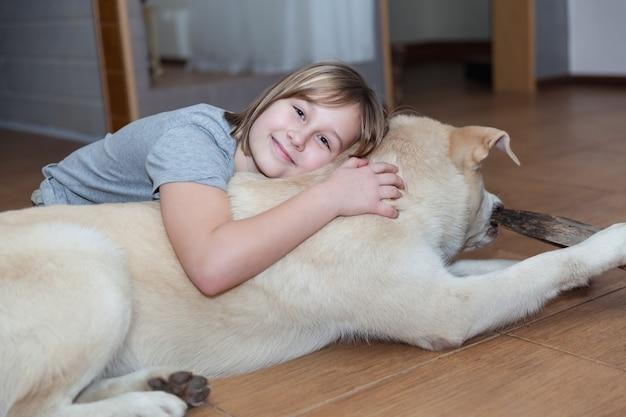 女の子は居間でラブラドールを抱きしめます。ソフトフォーカス