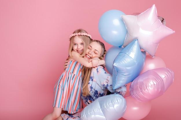 소녀는 분홍색 표면에 엄마와 미소를 안아