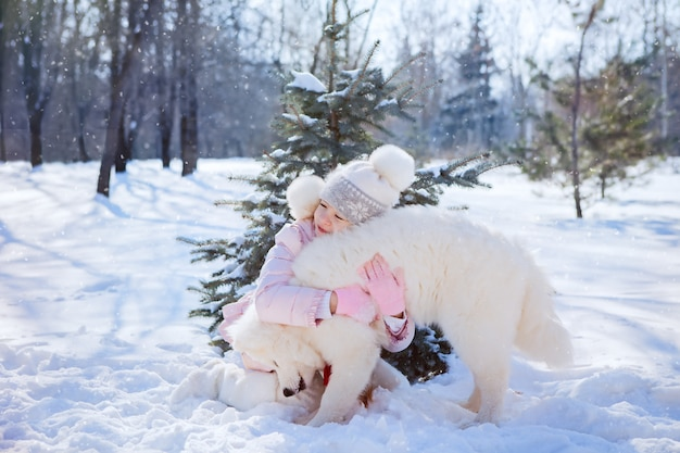 Girl hugs and plays with a samoyed dog in the snow under a small christmas tree in the park,