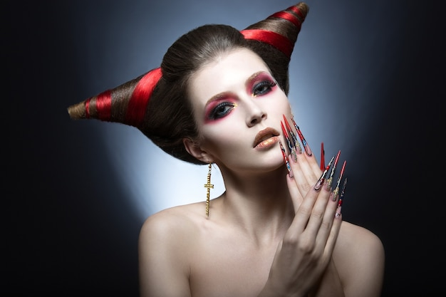 The girl in an image of the demon-tempter with long nails and haircut in the form of horns. picture taken in the studio on a gray background.