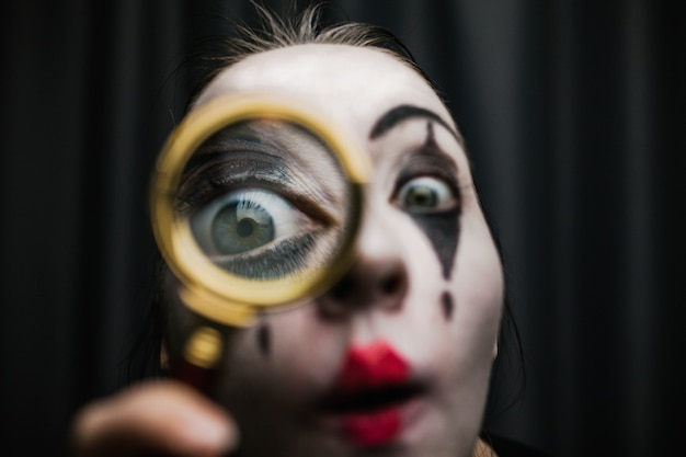 A girl in the image of a mime holds a magnifier.