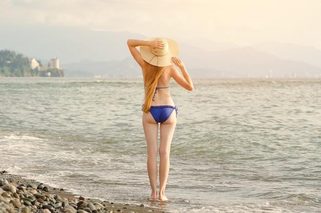 Девушка в купальнике и шляпе стоит у моря.