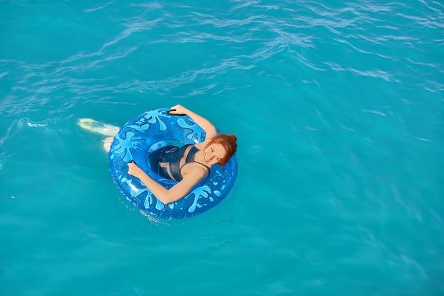 水着姿の女の子が膨らませてリングで海の上で休んでいる若い赤毛の女性が海に浮かんでいます...