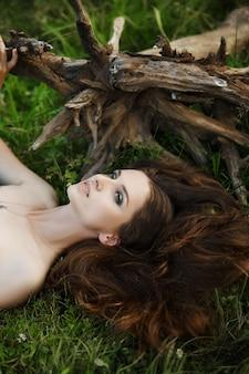 아름다운 녹색 드레스를 입은 소녀는 나무 뿌리 근처의 풀밭에 누워 꿈을 꿉니다. 자연 속에서 밝은 화장을 한 여성, 천연 화장품