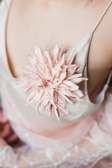 ピンクの花の花束を保持している美しいピンクのドレスの女の子。ミニマリズム