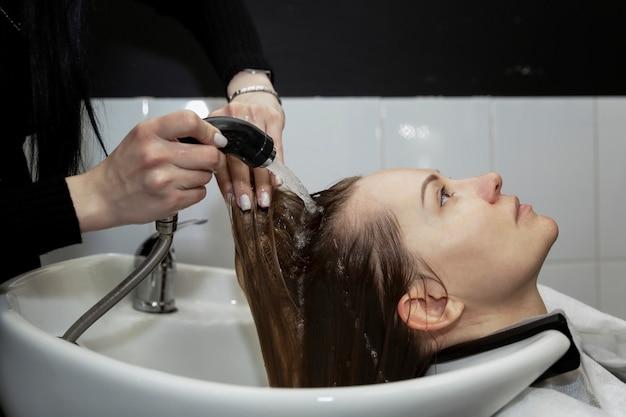 Девушка в салоне красоты моет волосы в раковине. крупный план.