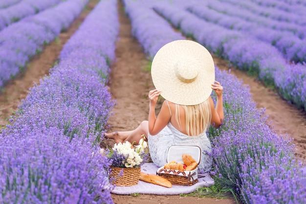 큰 모자에있는 여자는 라벤더 밭에 앉아있다. 피크닉에 여자. 뒤에서 사진.