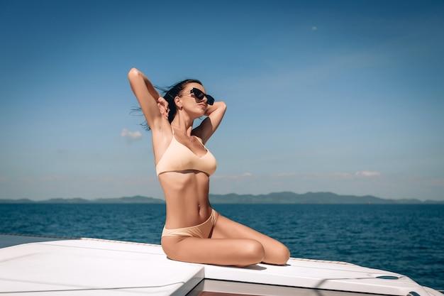 Девушка в бикини и солнечных очках сидит на своей огромной дорогой белой яхте и поднимает руки вверх, глядя в небо.