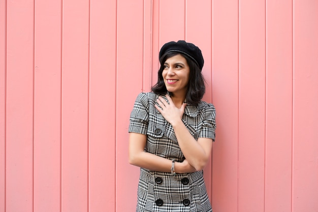 Девушка в черно-белом клетчатом платье и черной шляпе, смеясь перед розовой стеной.