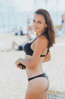 黒い水着の女の子、ビーチに立っている美しく魅力的な